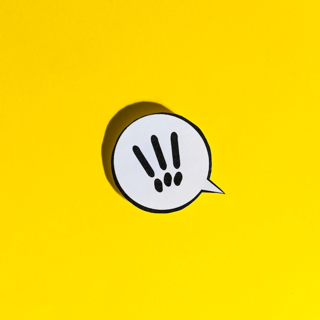 Exclamation mark icon speech bubble on yellow backdrop Free Photo