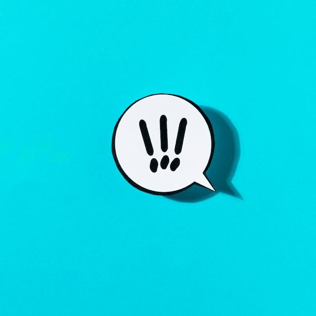 Exclamatory mark on white speech bubble against blue background Free Photo