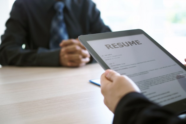 Executives are interviewing and watching the resume via tablet Premium Photo