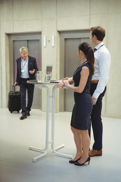 Руководители стоят со стаканами воды, чтобы поприветствовать своего коллегу Premium Фотографии