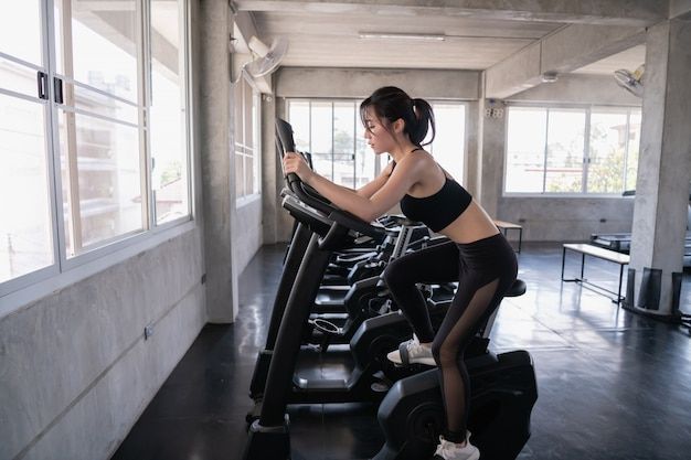 Exercise concept. beautiful girl exercising with a spinning exercise bike. beautiful girl exercising thighs for beautiful proportions. Premium Photo