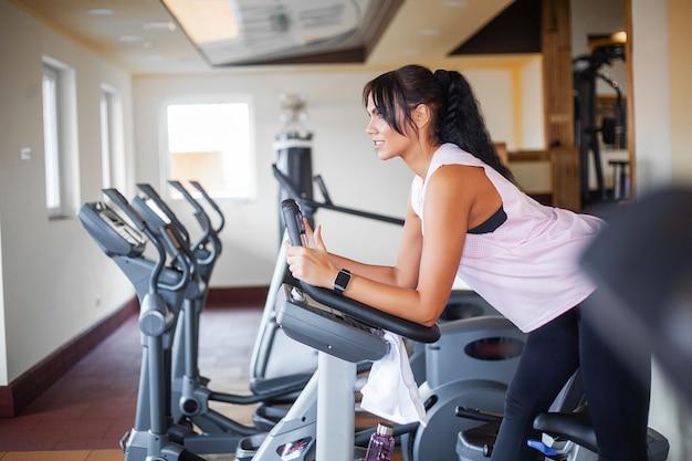Exercising legs doing cardio workout on cycling bike Premium Photo