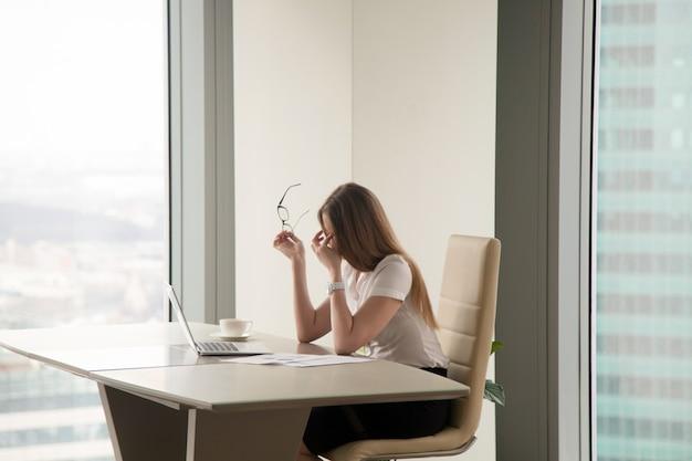 Вымотанная коммерсантка сидя на офисе Бесплатные Фотографии
