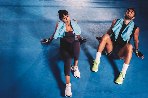 Exhausted couple on floor in gym Free Photo
