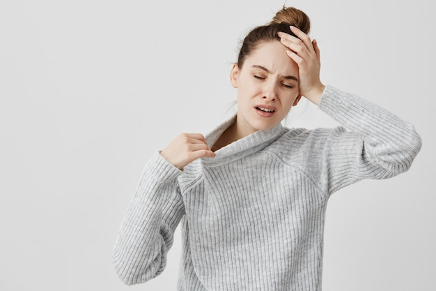 Exhausted girl holding her head with closed eyes being hot. female office assistant suffering from temperature and fever she needs fresh air. health concept Free Photo