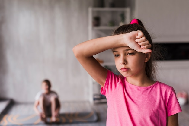 Exhausted girl with her hand on forehead standing in front of blurred boy at background Free Photo