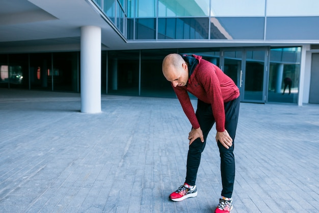 Exhausted male athlete standing outside the building Free Photo