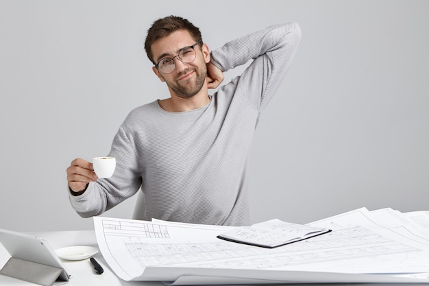 Architetto maschio oberato di lavoro esausto si siede alla scrivania, si allunga e beve caffè espresso Foto Gratuite