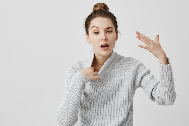 Exhausted woman gesturing with hand being warm pulling off her sweater. female shopper feeling heat standing in queue while making purchases at trade mall. body language Free Photo