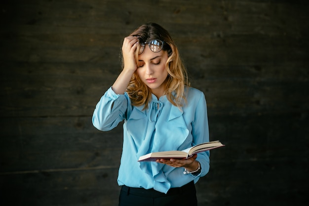 Exhausted woman looks tired, holds a book, keeps her head with hand Free Photo