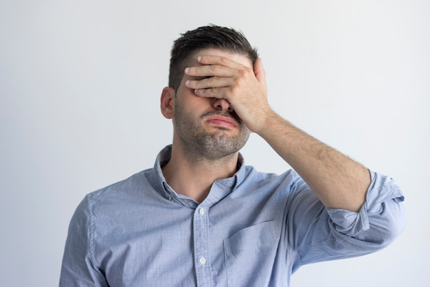Exhausted young man with stubble covering face with hand in despair. Free Photo
