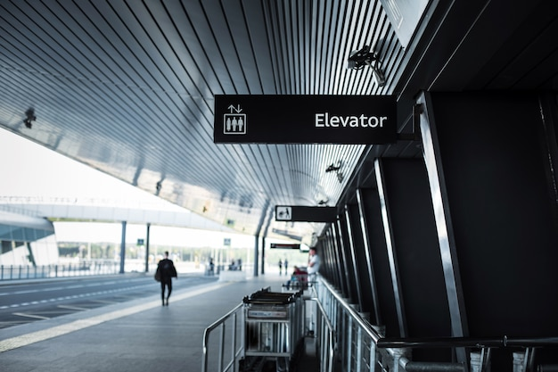 The exit of the airport pulkovo in saint-petersburg-the building of the airport with a signage and luggage trolleys and the road along it. Premium Photo