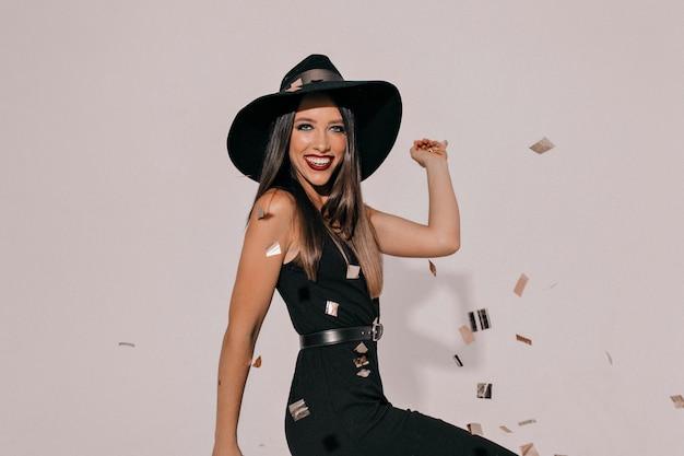 黒い帽子とパーティーを待っている暗い唇でエレガントな黒のドレスでアクティブな笑いブルネットの女性を終了 無料写真