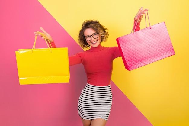 Вышедшая привлекательная женщина в стильной красочной одежде держит сумки для покупок с возбужденным счастливым выражением лица, эмоциональный, розово-желтый фон, шея поло, полосатая мини-юбка, распродажа, скидка, шопоголик Бесплатные Фотографии