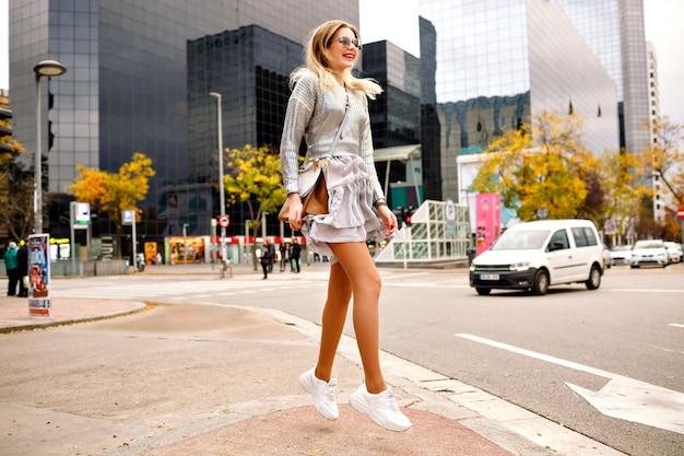 モダンな建物、スタイリッシュなエレガントなシルバーの衣装のスニーカー、高級バッグ、サングラス、ニューヨークで幸せな観光客の近くの路上で踊り、楽しい幸せな金髪女性を終了しました。 無料写真
