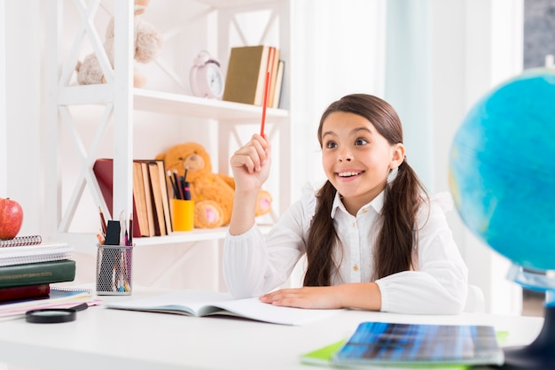 Exited child doing homework and finding solution at home Free Photo