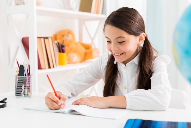 Exited cute schoolgirl in uniform studying at home Free Photo