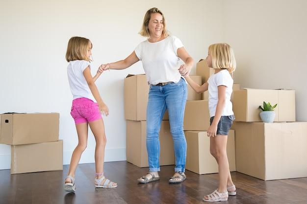 Madre uscita in piedi e mano nella mano di due ragazze tra scatole disimballate Foto Gratuite