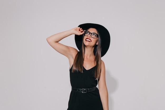 검은 드레스와 모자를 쓰고 안경을 쓰고 미소로 바라 보는 세련된 행복한 소녀를 종료했습니다. 무료 사진