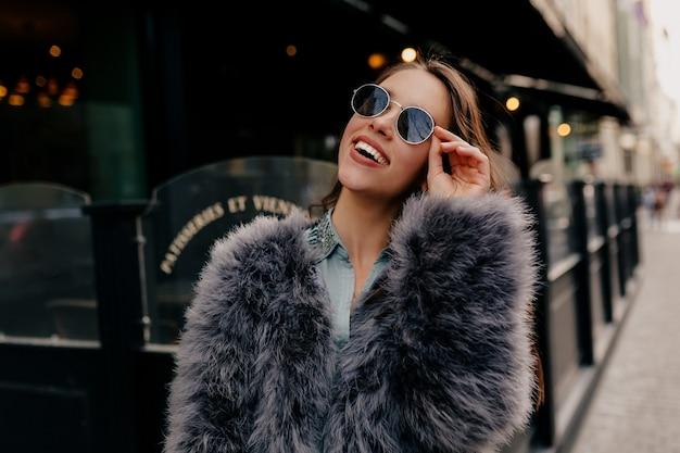 도시에서 트렌디 한 의상을 입은 세련된 여성을 종료했습니다. 모피 코트에 패션 초상화 예쁜 여자 무료 사진