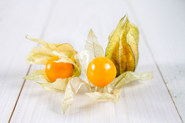 Exotic berries physalis on a white wooden table. Premium Photo