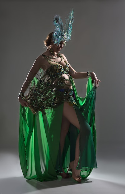 Exotic dancer in green costume with feathers Premium Photo