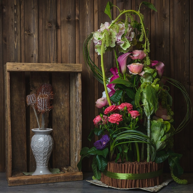 Exotic flower bouquet inside wooden basket wrapped with green ribbon. Free Photo