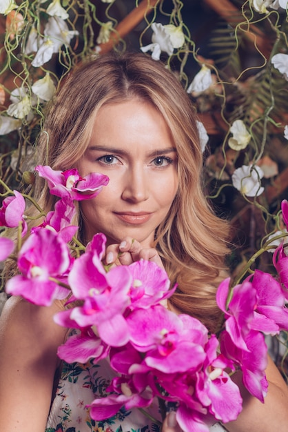 Exotic fresh orchid flowers in front of blonde young woman Free Photo