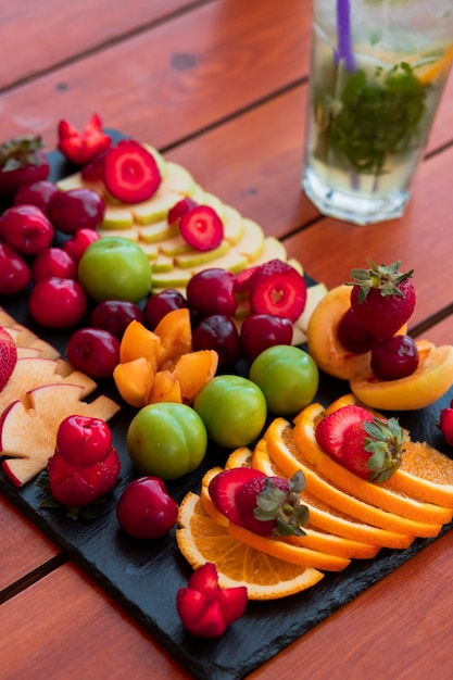 An exotic fruit platter and a glass of mojito Free Photo