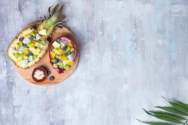 Exotic fruit salad served in half a dragon fruit and pineapple on round wooden plate on stone background, copy space. top view Premium Photo