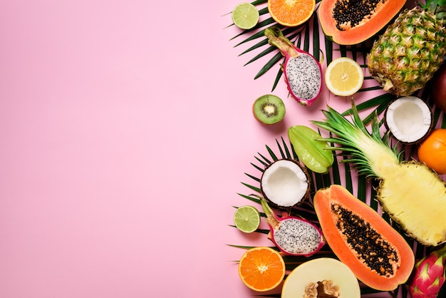 Exotic fruits and tropical palm leaves - papaya, mango, pineapple, banana, carambola, dragon fruit, kiwi, lemon, orange, melon, coconut, lime. Premium Photo