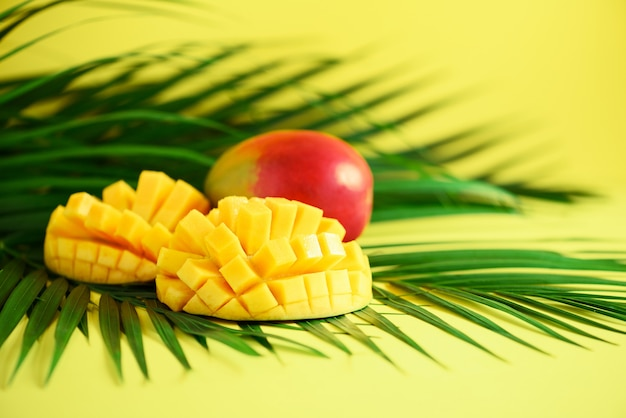 Exotic mango fruit over tropical green palm leaves on yellow background. pop art design, creative summer concept. banner Premium Photo
