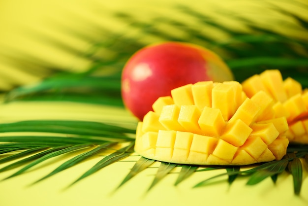 Exotic mango fruit over tropical green palm leaves on yellow background. pop art design, creative summer concept. Premium Photo