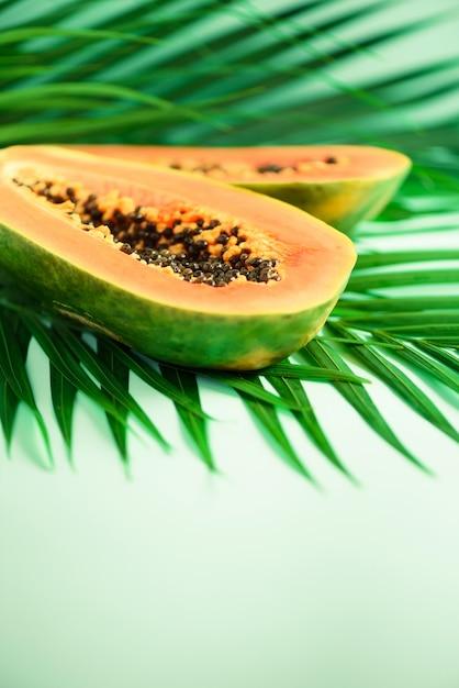 Экзотические фрукты папайи на тропических зеленых пальмовых листьев. поп-арт дизайн, концепция творческого лета. сырая веганская еда. Premium Фотографии