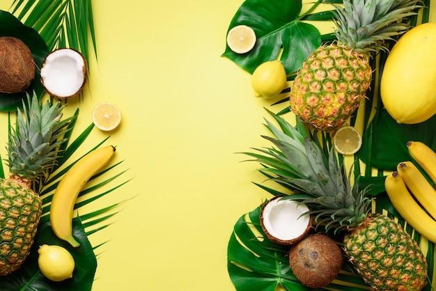 Exotic pineapples, ripe coconuts, banana, melon, lemon, tropical palm and green monstera leaves Premium Photo