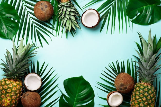 Exotic pineapples, ripe coconuts, tropical palm and green monstera leaves. Premium Photo