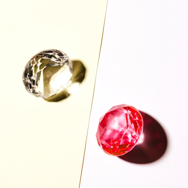 Expensive white and red diamond on white and beige backdrop Free Photo