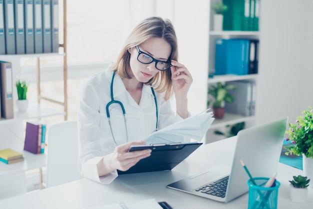 Опытный врач в белом халате, анализируя рецепт Premium Фотографии