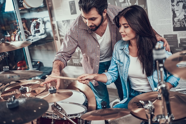 Experienced drummer teaches young girl playing drum set Premium Photo