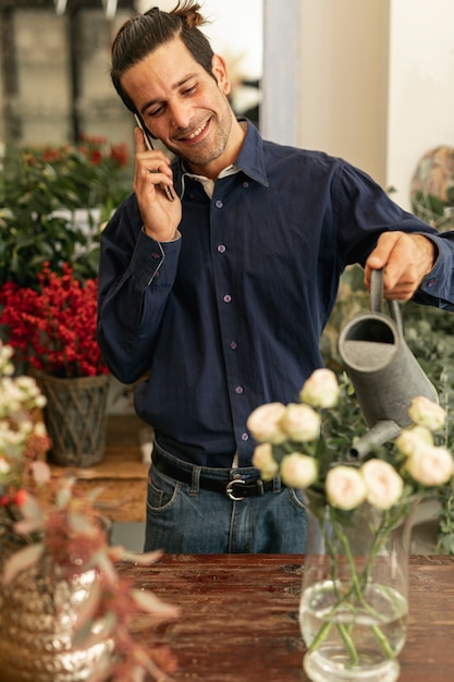 Experienced florist talking on the phone Free Photo