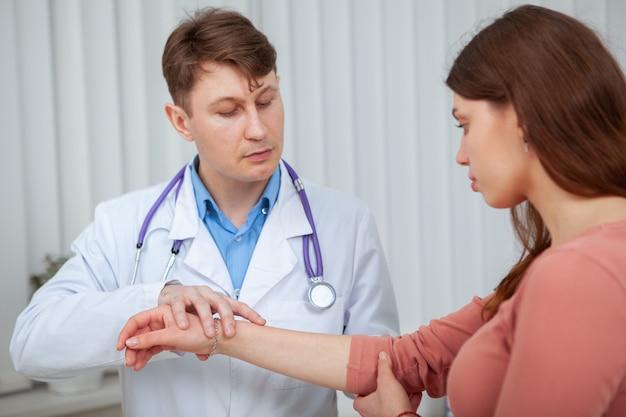 Опытный врач-мужчина осматривает травмированную руку пациентки Premium Фотографии