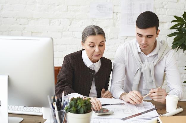Опытная зрелая женщина-архитектор с седыми волосами сидит на своем рабочем месте с молодым целеустремленным помощником-мужчиной, пересматривая чертежи и проектную документацию, используя калькулятор для проверки размеров Бесплатные Фотографии