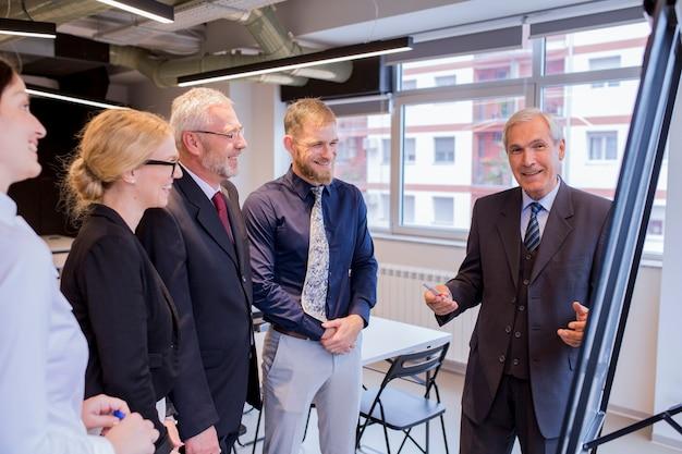 Experienced smiling businessman giving presentation to executive team Free Photo