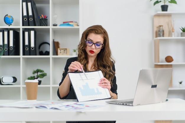 スタイリッシュな服とメガネをかけたビジネスウーマンの経験豊富で、ビジネスパートナーとビデオ通話で話し、グラフでレポートを示しています。 Premium写真