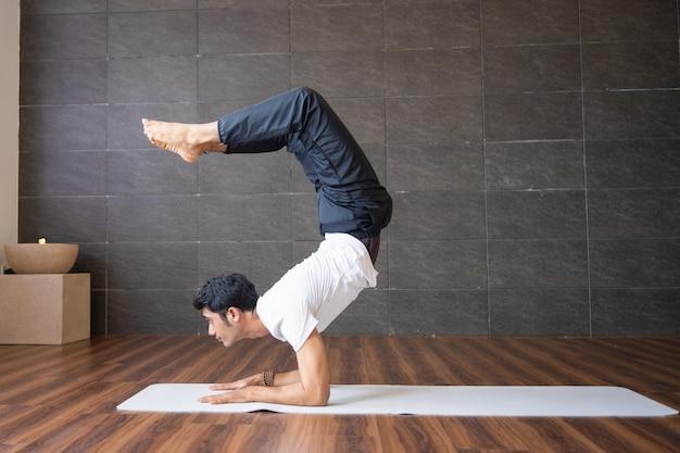 Experienced yogi doing scorpion yoga pose in gym Free Photo
