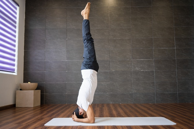 Experienced yogi doing supported headstand yoga pose Free Photo