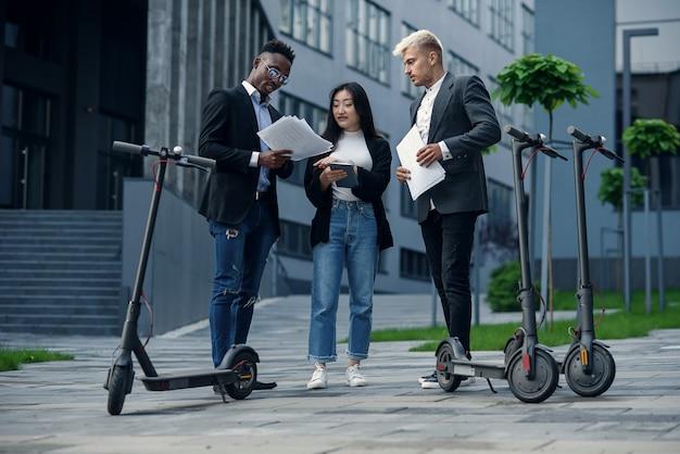 3人の同僚からなる経験豊富な国際ビジネスチームが、eの近くに立っているプロジェクトを分析します Premium写真