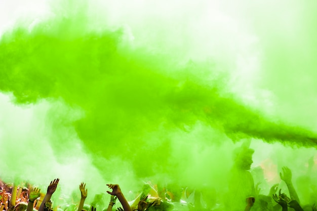 Explosion of green holi color over the crowd Free Photo