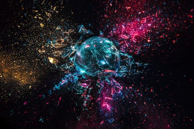 Взрыв стеклянного шара с цветными огнями, черный фон. высокоскоростная фотосъемка. Premium Фотографии