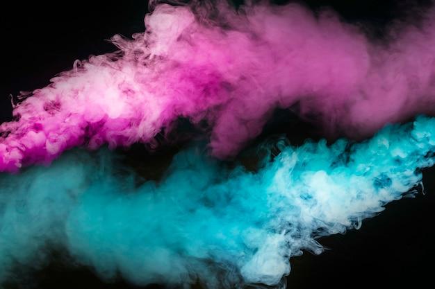 검은 배경에 파란색과 분홍색 연기의 폭발 프리미엄 사진